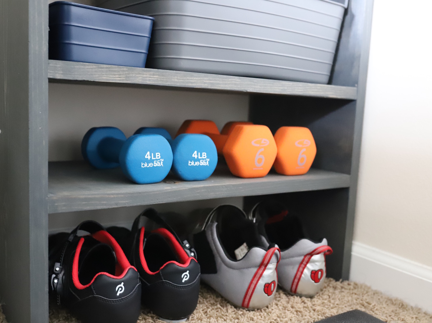 The shelf where we store our weights, towels, and spin shoes.
